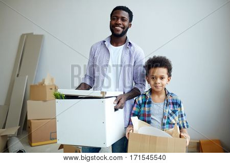 Young man and his son unpacking boxes after moving to new flat