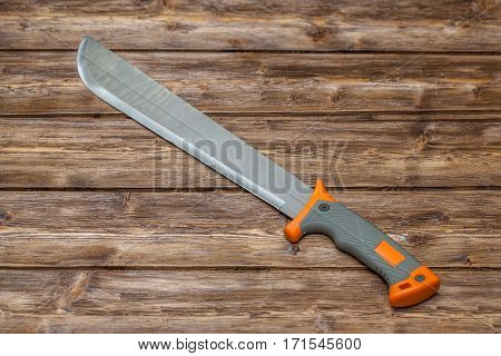 Machete for cutting grass on brown wooden background