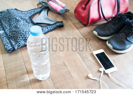 Bottle of water with mobile device and sport equipments on wood floor Healthy lifestyle concept