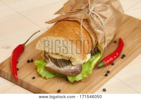 Big sub sandwich baguette with ham chili and lettuce on wooden cutting board closeup