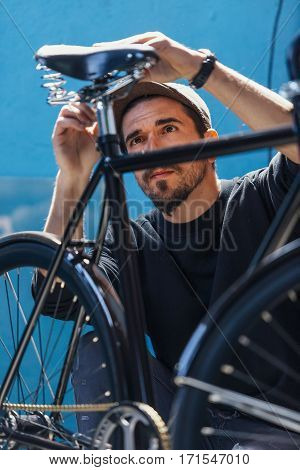 Bearded man in cap looking at bicycle and taking measurements