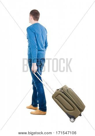 Back view of man with  green suitcase looking up. Rear view people collection.  backside view of person.  Isolated over white background. guy in the green t-shirt stands with a suitcase on wheels