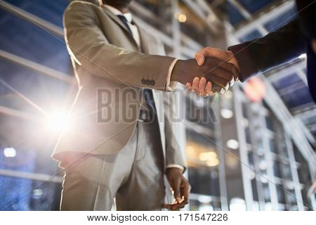 Two successful traders handshaking on background of modern construction