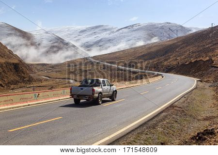 Pickup truck on the road Beautiful winter road in Tibet under snow mountain Sichuan China