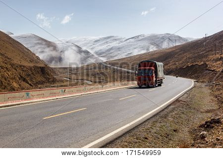 Truck on the road Beautiful winter road in Tibet under snow mountain Sichuan China