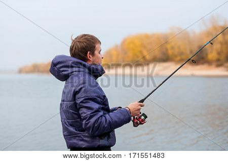 Man Holding A Spinning, Engaged In Fishing On The River