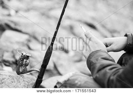 Fisherman Hand With A Cigarette Close-up, Waiting For A Man Smoking A Cigarette Looking At The Bait
