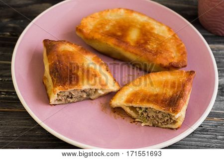 Pasties with meat and a mug of tea on a wooden table in a rustic style.