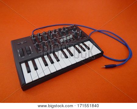 Electronic musical instrument or audio mixer or sound equalizer on a orange background with patch cables and headphones (analog modular synthesizer)