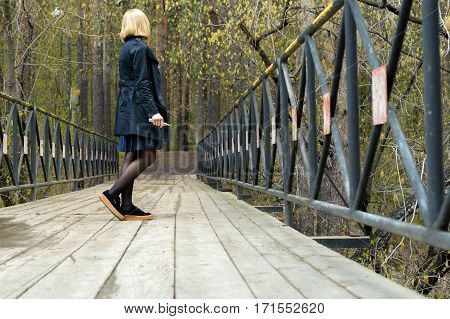 girl in a raincoat and sneakers on the bridge