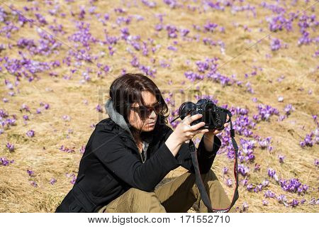 CHOCHOLOWSKA VALLEY, POLAND - MARCH 31, 2016: Attractive woman taking selfie against the background of flourishing crocuses. Chocholowska Valley Poland