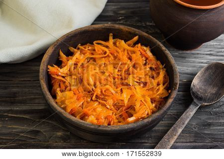 Braised cabbage in a wooden bowl on a wooden table in rustic style
