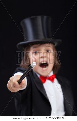 Young wizard or magician conjuring with magic wand on black background - focus on tip of wand