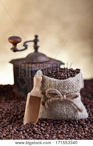 A bag of fresh roasted coffe and old grinder - on gold brown background
