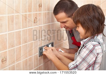 Electrician father teaching son how to install electrical sockets - copy space