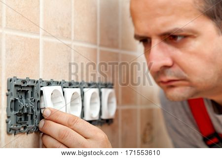 Electrician mounting the electrical wall fixture or plug components - placing the covering parts