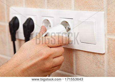 Electrician hand plugging a power cord into electrical wall fixture or socket - final tests