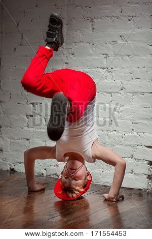 Portrait of cool young hip hop boy in red hat and red pants and white shirt standing on his head in the loft