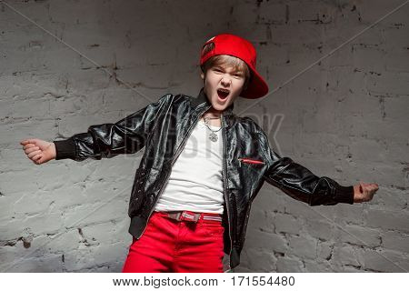 Portrait of cool young hip hop boy in red hat and red pants and white shirt and black leather jacket in the loft