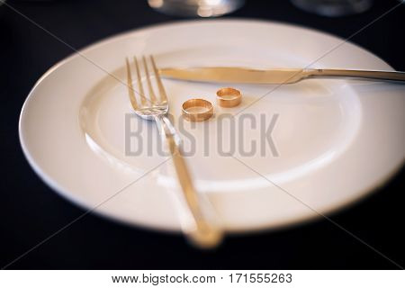 Two wedding rings lie on a white plate next to a knife and fork