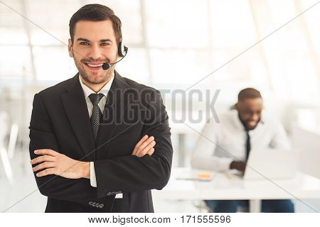 Handsome businessman in suit and headset is looking at camera and smiling his colleague is working in the background