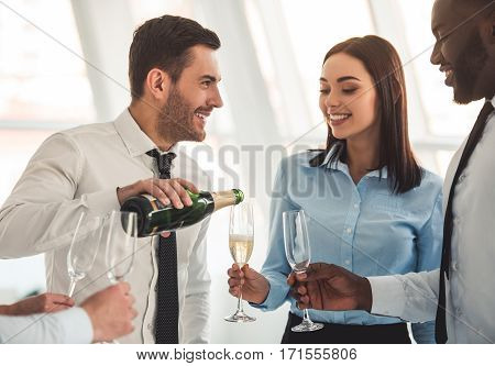 Successful business people are drinking champagne talking and smiling while celebrating in office