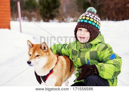 Little Boy With Shiba Inu Dog Outdoors
