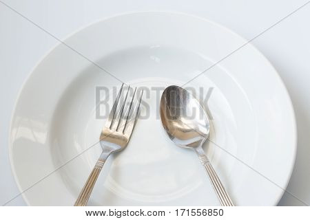 White dish with metal spoon and fork focus at center on gray background