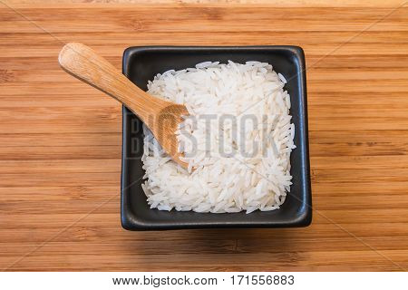 White rice in the black bowl with wood spoon on wood plate