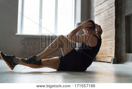 Young man workout in fitness club. Closeup portrait of caucasian guy making exercise, sit-ups and cross crunches for abs muscles, training indoors in window backlight