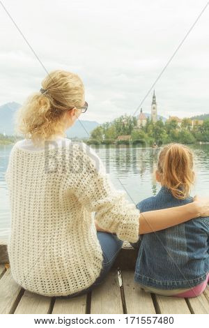 Mother and daughter enjoying the view on a lake.
