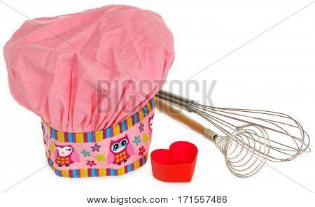 Pink cooking hat with multi-colored pattern hearts flowers and owls. Hearts molds for cookies in red. Whisk to froth and the egg whisk with wooden handles. The pattern on the cap in the colors yellow orange red blue purple. Chef cap on a white background