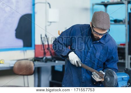 Adult man in cap working with metal designing bicycles.