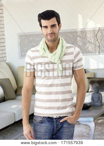 Casual young man standing at home hand in pocket, smiling, looking at camera.
