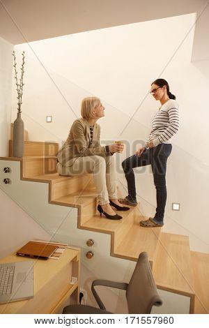 Female friends talking in stairway, drinking tea. Full size.