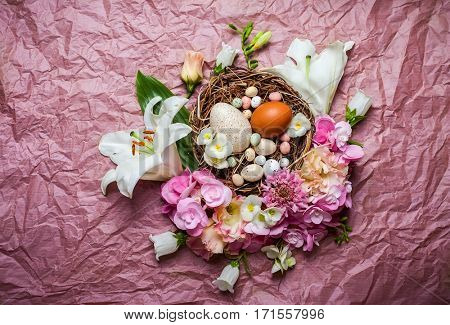 Easter composition with festive flowers decoration and traditional treats : easter chocolate candy mini eggs in bird nest. Top view with copy space