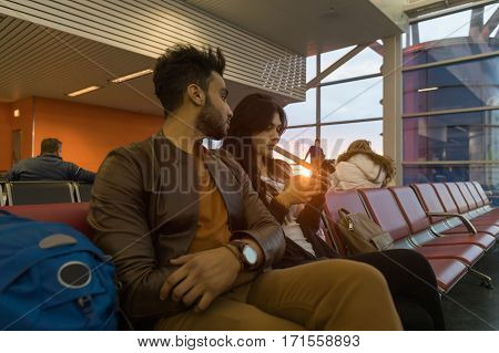 Young Couple Sit In Airport Lounge Waiting Departure Hispanic Man And Woman Use Cell Smart Phone Flight Delay