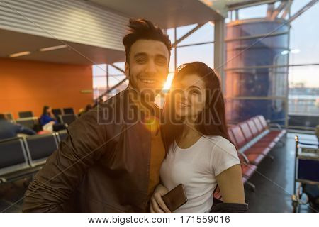 Young Couple In Airport Lounge Waiting Departure Happy Smile Hispanic Man And Woman Flight