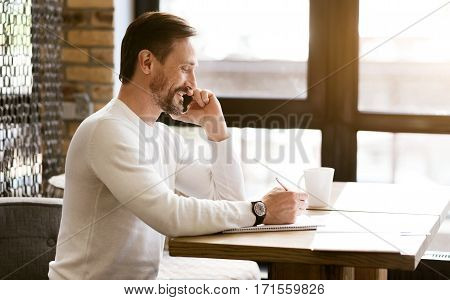 Enjoying conversation with my business partner . Smiling charming bearded businessman sitting at the table in the cafe and working while talking over the phone and taking notes