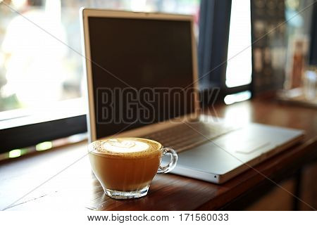 laptop with fresh cup of coffee in coffee shop