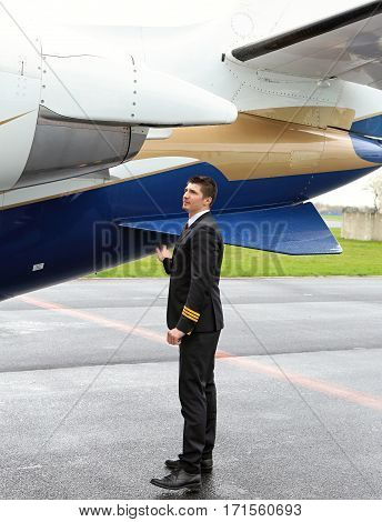 Young first officer pilot checking exhaust of the small jet engine