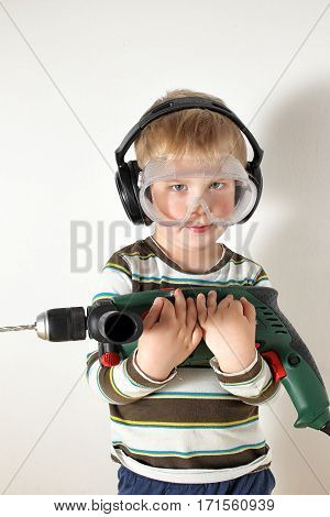 Small boy holding drilling machine with protective glasses and hearing protection