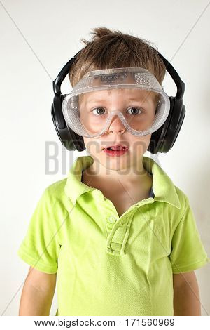 Small boy wearing protective glasses and earphones