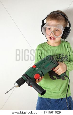 Boy with green shirt and drilling machine wearing eyes and hears protection ready to drill