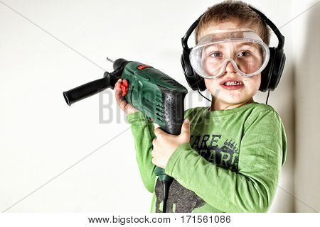 Boy with eyes and ears protection holding drilling machine on his shoulder
