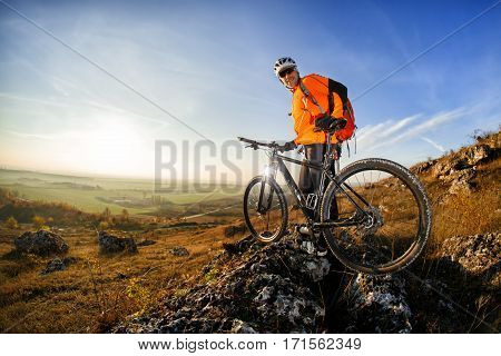 Cyclist on the top of a hill with blue sky clouds. Cyclist in the orange jacket, helmet and sunglasses, with red backpack. Wide angle and fisheye. Beautiful landscape with sky, rocks and hill. Travel in the countryside. Spring season.