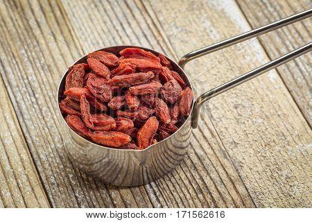 dried goji berries in a metal measuring scoop against grunge wood background