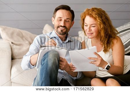 Concentrated on the successful result. Merry creative positive couple sitting at home and having conversation while expressing interest and taking notes