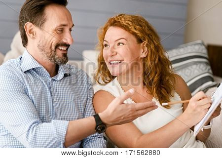 Amused from our discussion. Funny smiling positive couple sitting at home and having conversation while expressing positivity and taking notes