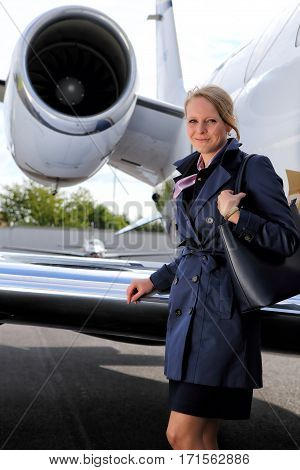 Blonde flight attendat in the coat with the handbag under the jet engine